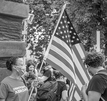 Black and white image of masked woman carrying an American flag